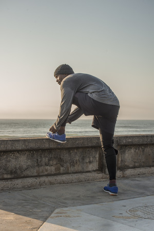 A jogger in grey and black dress pauses to tie his shoes at a low wall by the side of the road near the ocean.