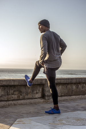 A jogger stops by the walkway next to the ocean to do some stretch exercises.