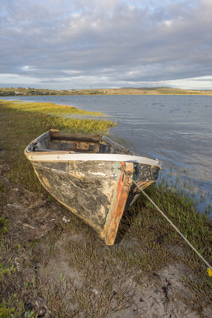 An old hull of a motorboat lies tied to the bank of a river as it is viewed from the front. Stock Photo