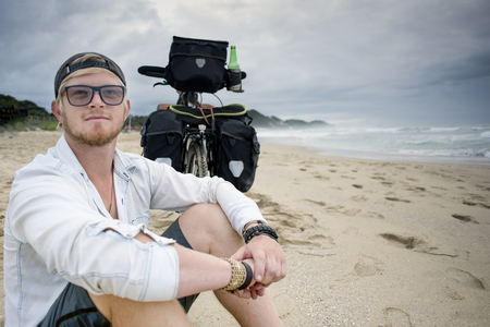 A long distance cyclist sits on the beach with his arms on his legs, looking out in to the distance while his bicycle with panniers stand behind him. Stock Photo
