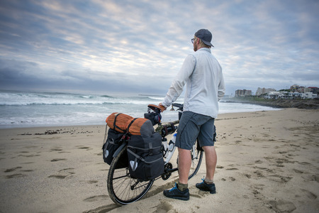 A young man stand on  the beach, viewing the ocean, while holding his long distance bicycle with tent and panniers in his hands, as he is viewed from behind.