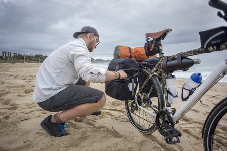 A long distance adventure cyclist prepares the panniers on his bicycle while on the beach.