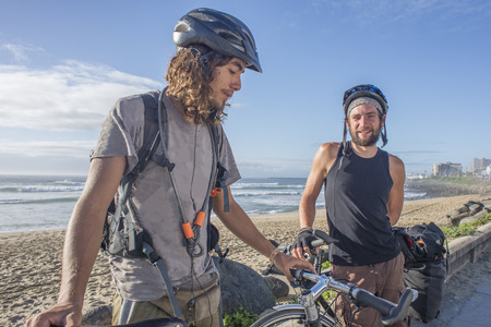 Two adventure long distance touring cyclists stand with their bicycles by the beach and ocean.