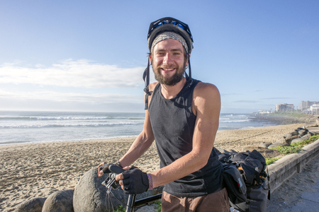 Portrait of a long distance adventure touring cyclist by his bicycle next to the beach. Standard-Bild