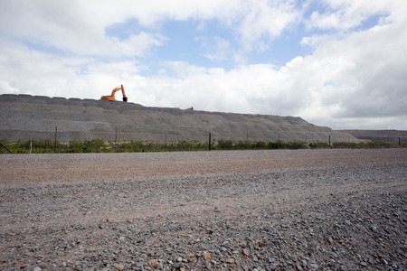 View of a new road under construction with a front end loader at work in the far distance on top of a hill of material.