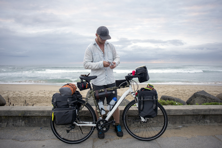 A long distance cyclists closes a tool in his hand as he stands by his packed bicycle with the ocean in the background.