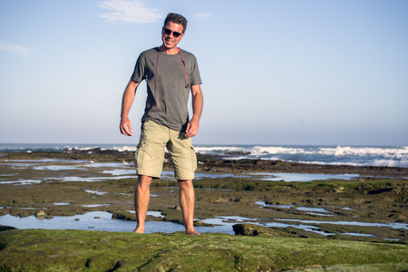 Full length portrait of a smiling man in shorts and T shirt on the rocks by the ocean. Standard-Bild