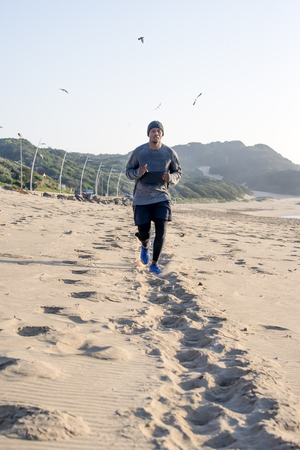 A view of a man jogging along the beach as he approaches along a path on the sand.