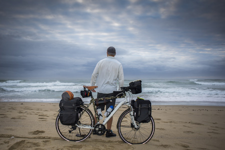 A long distance adventure cyclist stand on a beach in front of his bicycle, with his back to viewer, as he looks at the ocean.
