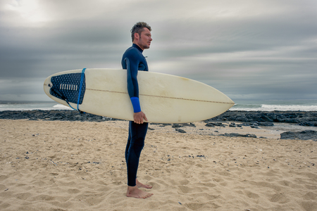 A full length portrait from the side of a surfer standing on the beach with surfboard under the arm as he looks towards the ocean.