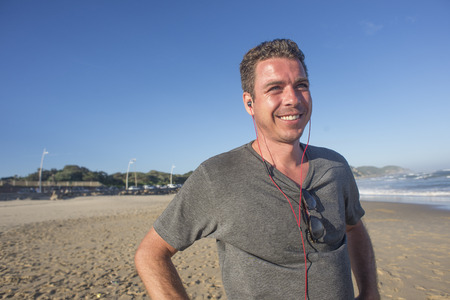 Half length portrait of a man with earphones in ears standing on the beach with a smile as he listens to music and viewing the ocean. Standard-Bild