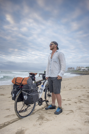 A long distance adventrure cyclist stand on the beach with his packed bicycle beside him as he looks out over the ocean.