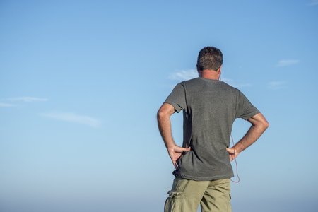 Three quarter view of the back of a man looking away, set against a blue sky with some clouds.