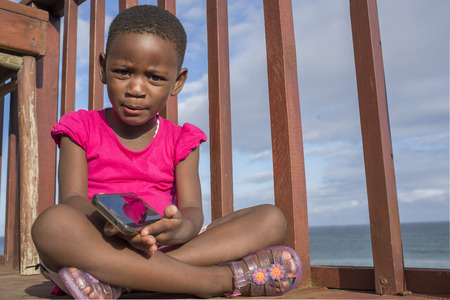 A little girl sits on a wooden deck overlooking the ocean while holding a mobile phone in her hands. Standard-Bild