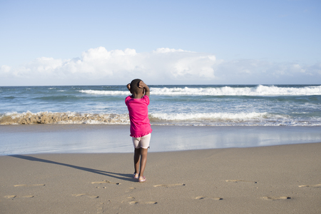 A little girl stand with her back to the viewer while watching the waves roling in on the beach. Standard-Bild