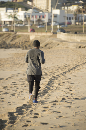 A view of a man jogging on the beach away from the viewer with the town in the background.