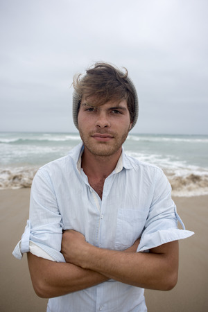 A front view of a young man in his early twenties on the beach on a cloudy day with sea in background as he looks towards the camera with his arms folded.
