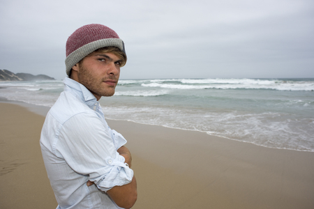 A young man in his mid twenties stand on the beach on a cloudy day while looking towards the viewer.
