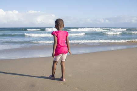 A little girl whearing a bright pink top stands on the beach with her back to the viewer while looking towards the ocean. Standard-Bild