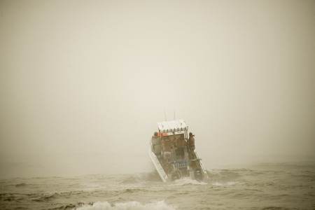A motor boat for deep sea fishing launches in the waves and the mist .