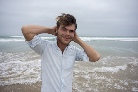 A young man stands in front of the sea with arms behind his head and smiling at the camera.
