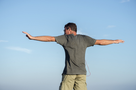 A man, viewed from behind against a blue sky, stretches his arms out to his side. Stock Photo