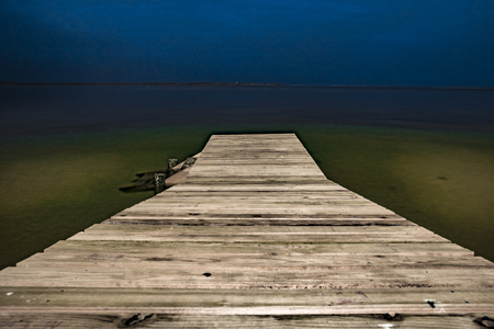 A wooden walkway leads in to a lagoon as viewed at night time.