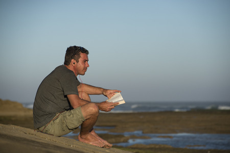 A man sits on a rock overlooking the ocean while listening to music and reading a book similtaniously