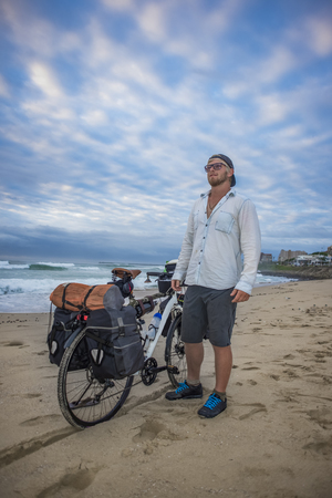 A long distance cycle packer stands on the beach by his packed bicycle while viewing the ocean.