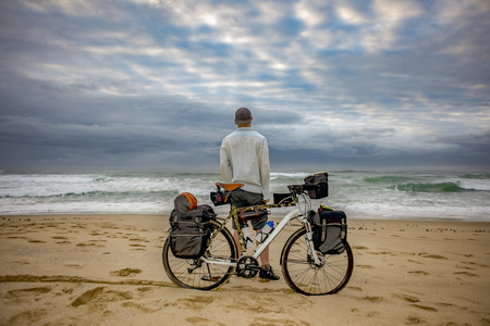 A cycle packer long distance cyclist stand in front of his bicycle on the beach while looking at the ocean. Standard-Bild