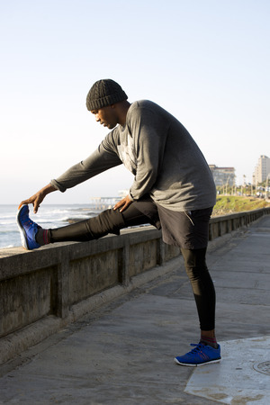 A jogger does some leg stretches by the side of the road near the ocean.