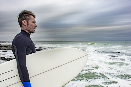 A side portrait of a surfer, with his surfboard under his arm as he views the ocean.