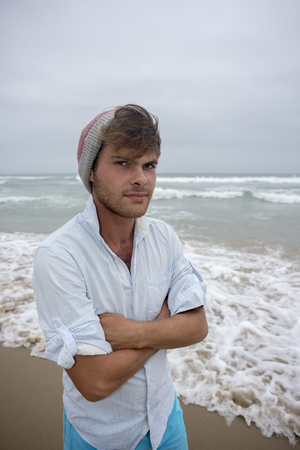 A young man in his early twenties stand by the ocean on the beach on a cool day with a beeny on his head and his arms folded. Standard-Bild