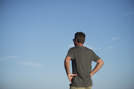 Three quarters view from low down of the back of a man with blue sky as backdrop as he stands with his hands on his hips.