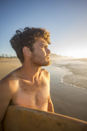 A vertical portrait of a young surfer in his early twenties standing on the beach, by the ocean, with his board under his arms, as he looks out towards the sea ad surf with the early morning sun falling on his face.