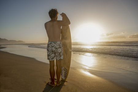 A young surfer stands with his board on the beach at daybreak and investigates the ocean for some good surf.