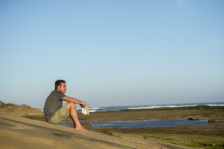 A man in his fourties sits on the rocks by the ocean with a book in his hand while watching the ocean and listening to some music with earphones.