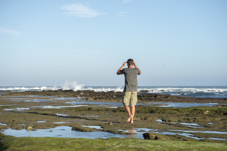 A man in his forties walks along on the rocks by the ocean Standard-Bild