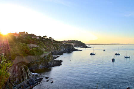 Collioure coastline at sunset with boats sailing on a calm Mediterranean sea