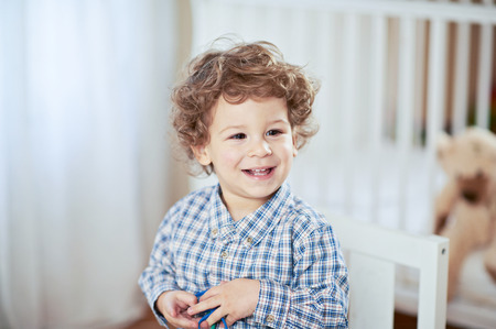 babyroom: Portrait of happy smiling beautiful little boy in babyroom - checked shirt