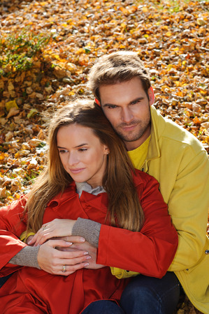 Love couple embracing and loving in season - autumn park, coloursfull leaves, pregnant woman, smiling healthy couple, sunny day Stock Photo