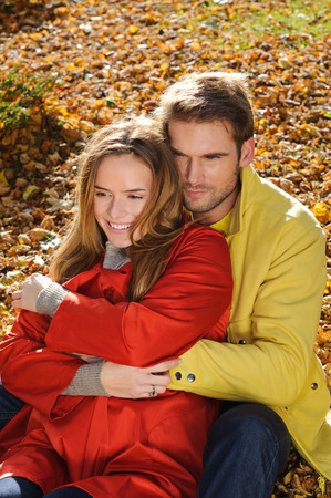 Young couple in the park in a fashion shot, both looking away - autumn, park, leaves