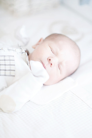 Adorable newborn baby sleeping on back