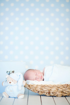 Picture of a newborn baby curled up sleeping in a basket on a blanket
