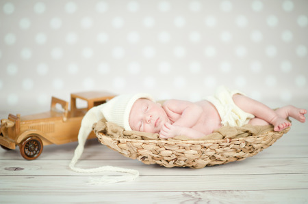 Immagine di un neonato che dorme rannicchiato in un cesto Archivio Fotografico - 35837626