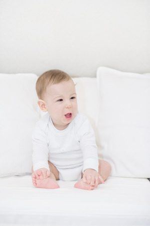 Portrait of crying baby boy in white. Little Angel photo