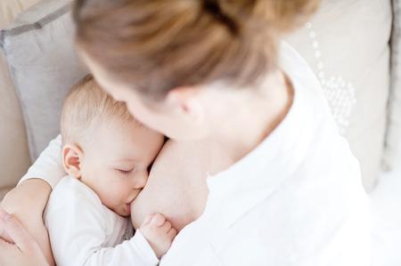 beaux seins: Jeune mère allaitant le bébé de newborm - intérieur