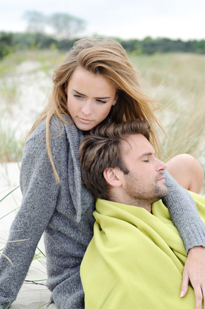The attractive lovely woman and man sit in the sand dune of a beach relaxing - autumn, beach, sea photo