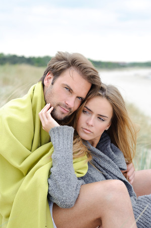 Couple embracing each other at the beach in background autumn sea and sand dune photo