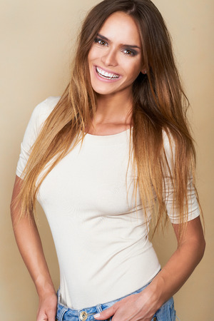 Nice looking smiling woman with brown top on brown isolated background